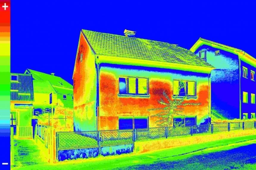 Termovizní snímek fasády domu. Červená a oranžová místa ukazují oblasti velkých tepelných ztrát