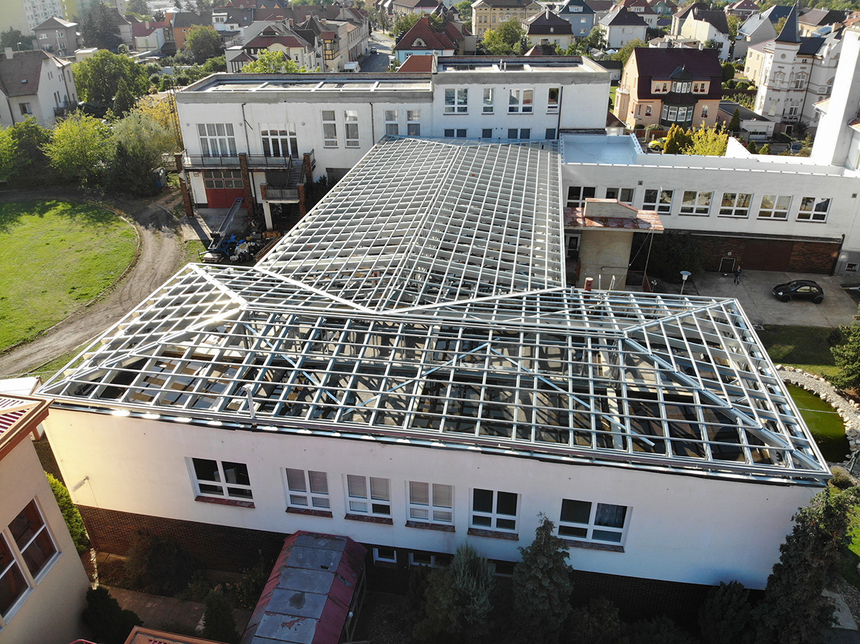 rekonstrukce ploché střechy na šikmou na budovách Obchodní akademie a SOŠ v Žatci.