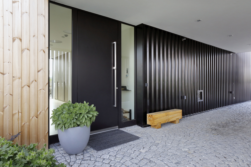 Vchod do domu, který je sazen černou fasádou a střechou z trapézů Lindab