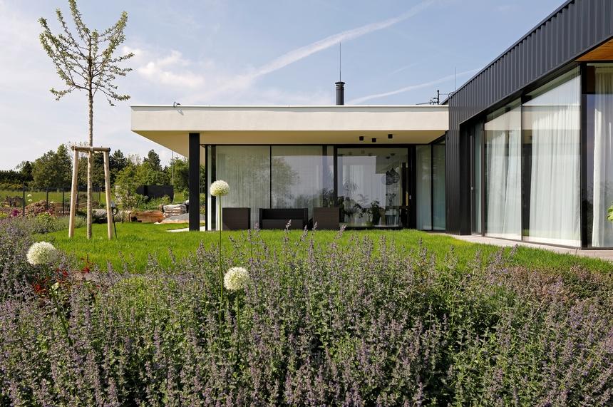 Pohled ze zahrady na dům z trapézů lindab