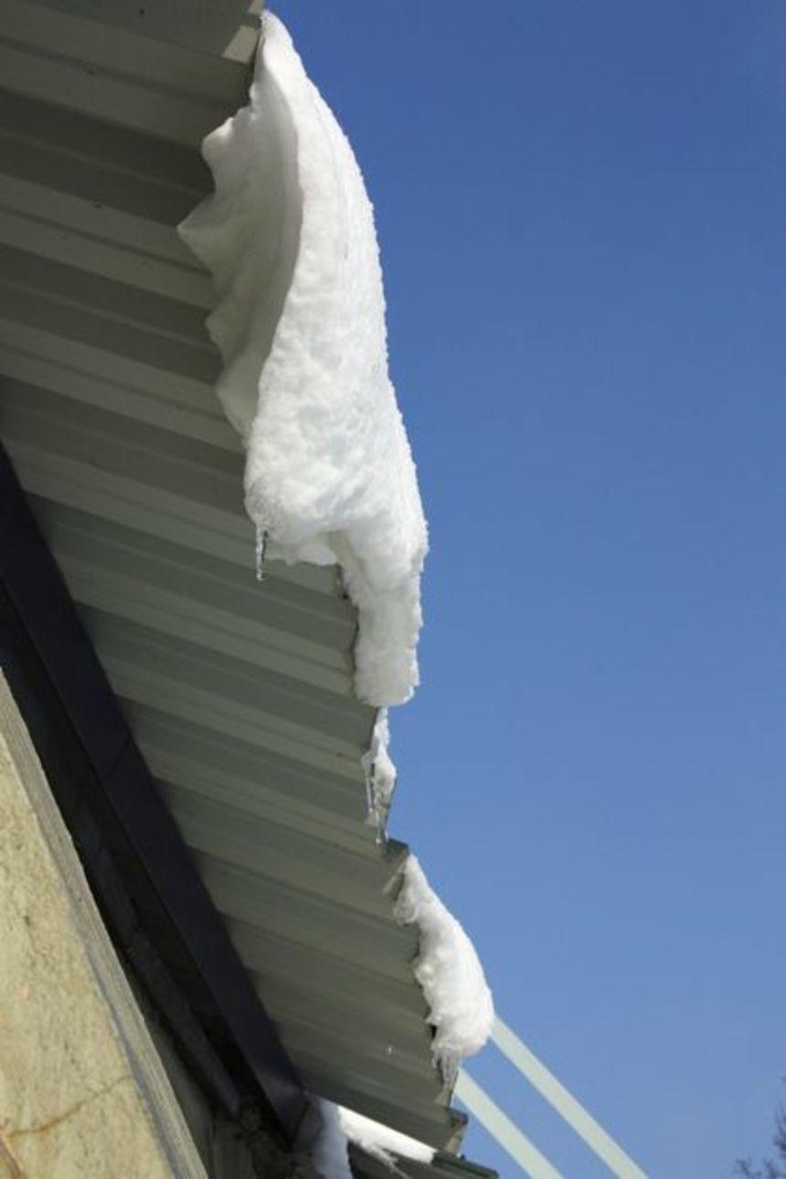 Masa sněhu u okapu, sjíždějící po trapézovém plechu